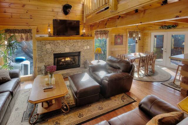 cabin living room with fireplace and view
