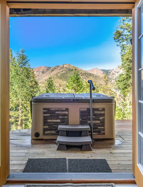hot tub outside of cabin back doors on deck with views