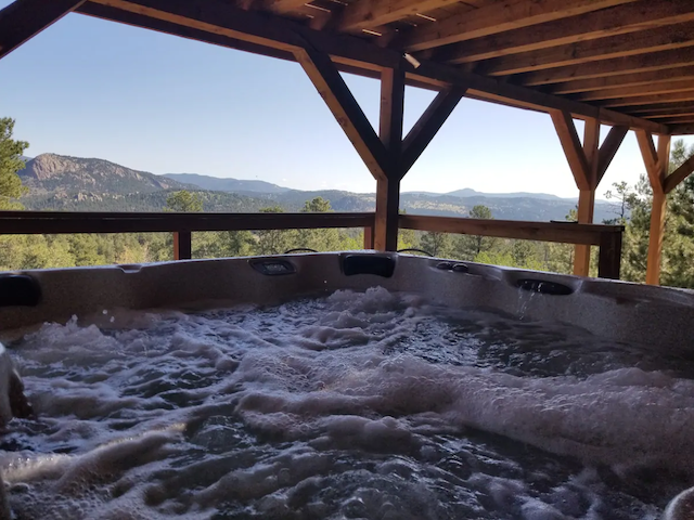hot tub on covered deck with mountain views