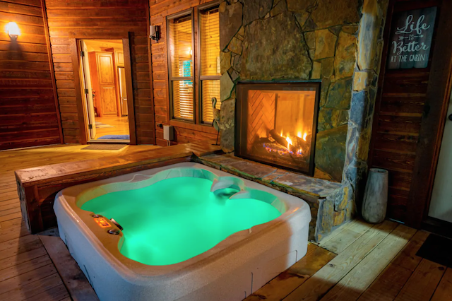 hot tub next to fireplace outside Kiss Me On the Creek Cabin